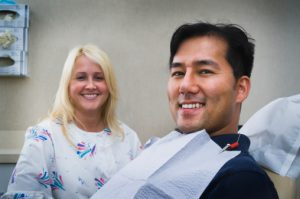 Female dentist smiling with man in chair